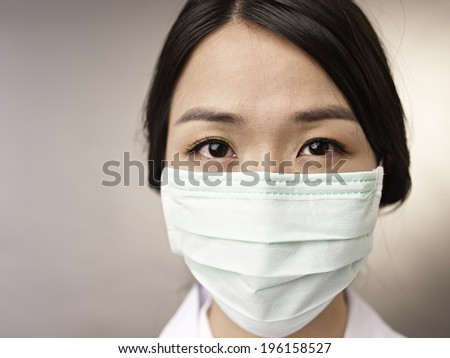face of a woman wearing a mask. - stock photo