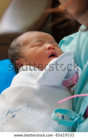 Face of Asian female newborn fall asleep in mother's arms vertical - stock photo