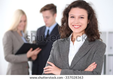 Face of beautiful cheerful smiling business woman on the background of business people Successful business concept - stock photo