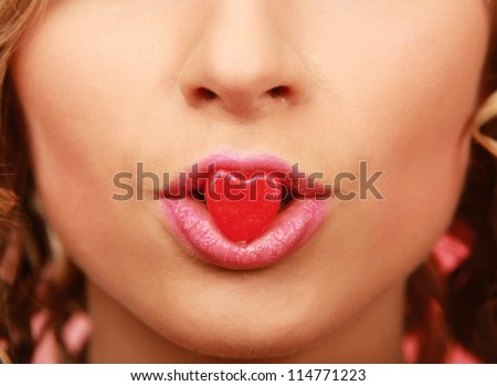 face of beautiful girl smiling and holding a little heart - stock photo