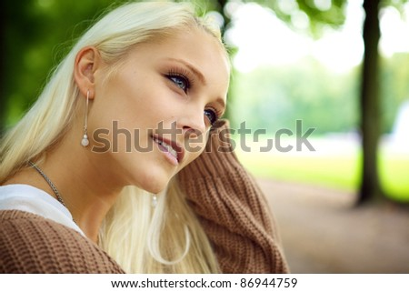 Face of beautiful young blonde female model daydreaming in wistful contemplation in a park. - stock photo