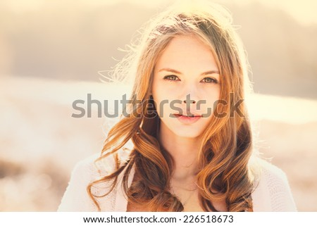 face of beautiful young smiling girl in a sunny day - stock photo