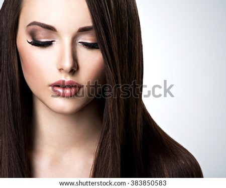 Face of beautiful young woman with brown make-up and  straight  hair - stock photo