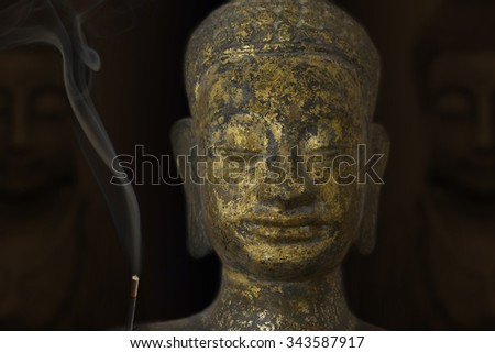 Face of Buddha with gold and incense - stock photo