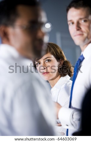 Face of businesswoman, 40s, looking out between two men standing beside - stock photo
