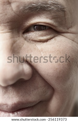 Face of elderly man looking at camera. Vertical photo - stock photo