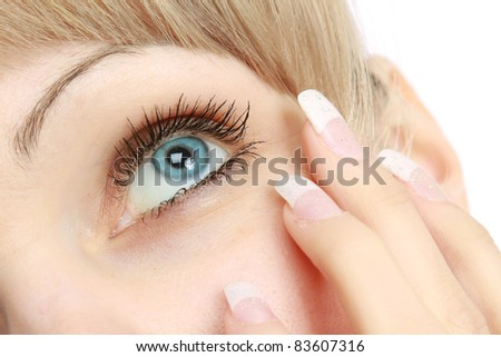 Face of girl applying cosmetic cream on skin around eyes - stock photo