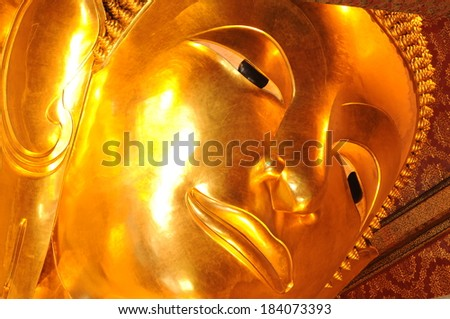 face of golden reclining buddha statue. Wat Pho, Bangkok, Thailand  - stock photo
