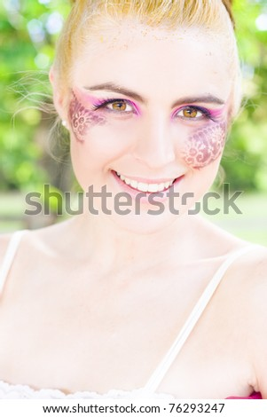 Face Of Happiness See A Blond Woman In Creative Flower Or Floral Cosmetics Smile In Joy While Standing Outdoors At A Lush Green Nature Reserve - stock photo