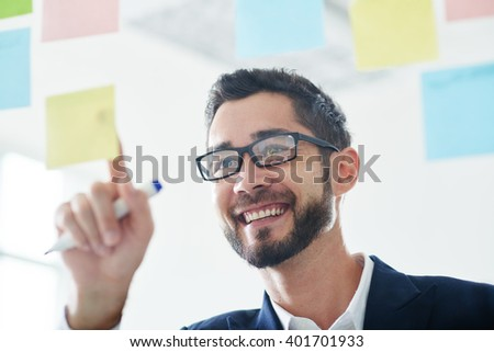 Face of happy creative businessman sticking notes on the wall - stock photo