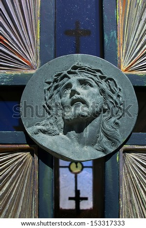 Face of Jesus Christ carved on a bronze cemetery gate. - stock photo