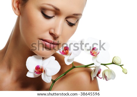 Face of pretty beautiful woman with a white orchid on her shoulder - stock photo