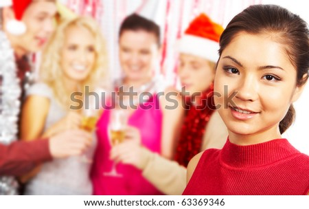 Face of pretty girl looking at camera with smile on background of her friends partying - stock photo