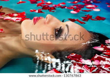Face of pretty woman floating in swimming pool with petals of rose - stock photo
