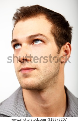 Face of serious man looking up over white - stock photo