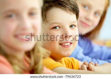 Face of smart schoolboy looking at camera between girls - stock photo