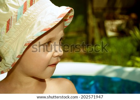 Face of the boy in panama hat with funny smile in an inflatable pool. - stock photo