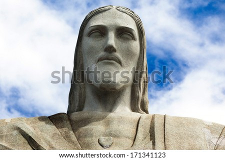 Face of the statue of Christ the redeemer in Rio de Janeiro against blue sky - stock photo
