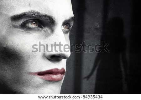 Face of vampire on a dark grungy background with woman shadow - stock photo
