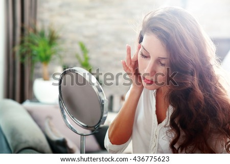 face of young beautiful healthy woman looking in the mirror - stock photo
