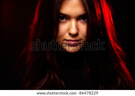 Face of young woman in the dark - stock photo