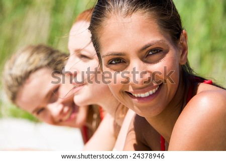 Face of young woman looking at camera on hot summer day with her friends at background - stock photo