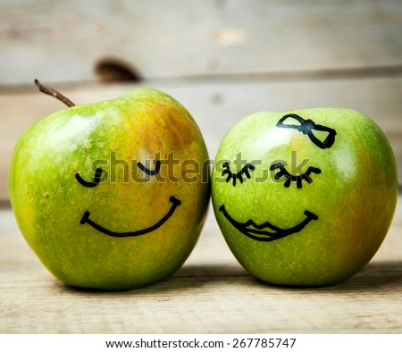 Face on a green apple. Couple in love. Wooden background - stock photo