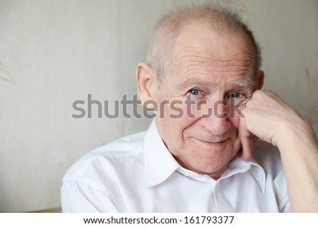 face portrait of a cheerful smiling senior man with his arm near his face - stock photo