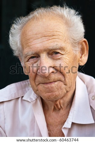 face portrait of a senior man on a black background - stock photo