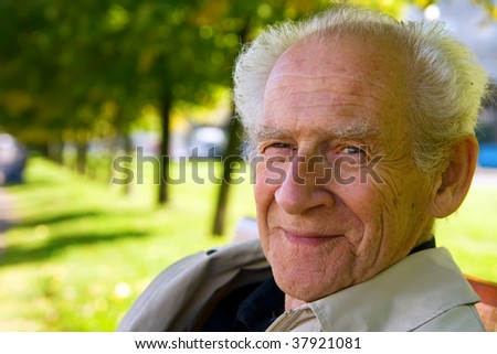 face portrait of an old smiling man - stock photo