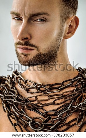 Face powerful slave male bearded warrior with metal chains on neck. Gladiators concept - stock photo