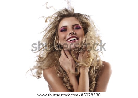 face shot of a laughing curly blonde throwing her hair in the wind - stock photo