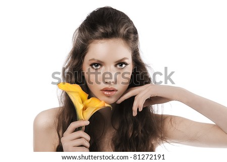 face shot pf a pretty young girl with curly brown hair holding a yellow calla in her hand - stock photo