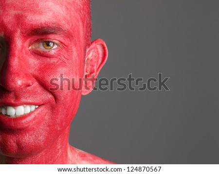 Face smiling man makeup red isolated on dark background - stock photo