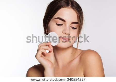 Face treatment, beautiful young girl with perfect skin is cleaning face with cotton pads, cosmetics concept - stock photo
