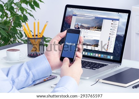 Facebook app on the Apple iPhone display and desktop version of Facebook on the Apple Macbook Pro Retina. Multi devices multitasking concept. All gadgets in full focus. Varna, Bulgaria - May 29, 2015. - stock photo