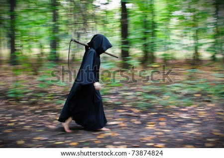 Faceless Death in black robe with scythe walking through the forest - stock photo