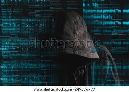 Faceless hooded anonymous computer hacker with programming code from monitor, deep web concept - stock photo