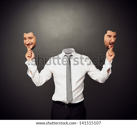 faceless man holding masks with good and bad moods - stock photo