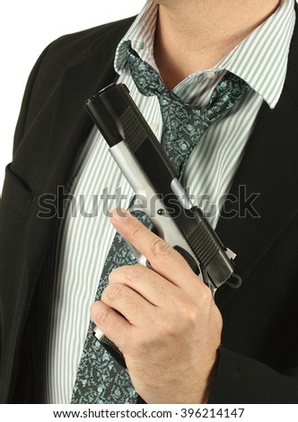 Faceless man in a suit holding a gun - stock photo