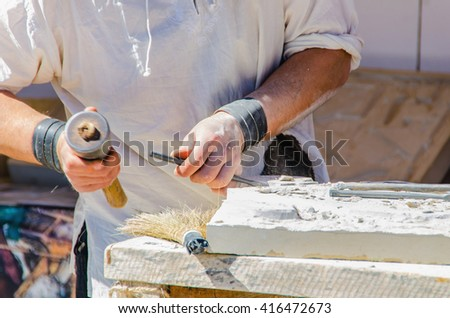 Faceless man working with chisel. Sculpting on stone - stock photo