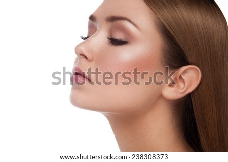 Facial beauty portrait of young girl with chestnut hair, natural make up with head to the left and looking down on white background - stock photo