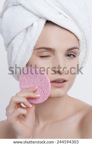 Facial funny portrait  young lady with natural make up, french manicure and clear skin with white towel on her head and pink rough sponge in her left hand closing her left cheek turning her  - stock photo