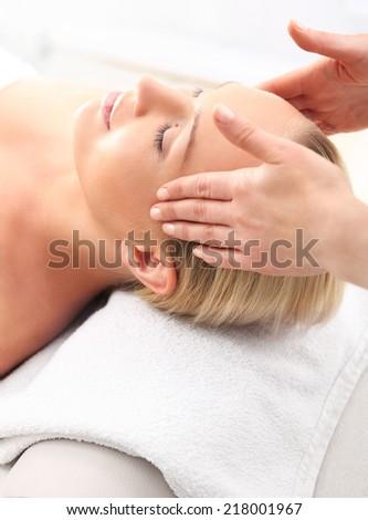 Facial massage .Beauty salon, the woman at face massage . Attractive blonde woman in spa salon  - stock photo
