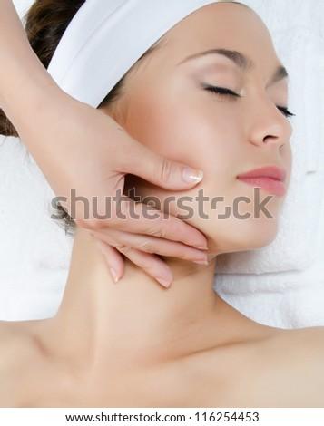 Facial massage to the woman close up - stock photo