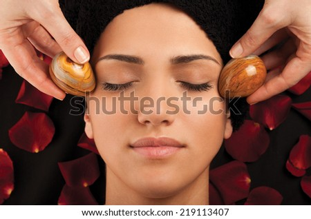 Facial massage with special marble eggs of a young woman. - stock photo