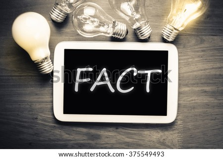 Fact topic on mobile tablet with glowing light bulbs on the table - stock photo