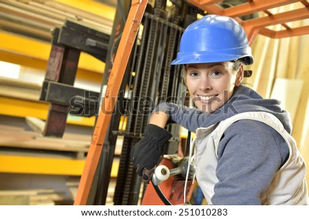 Factory operator in warehouse using storage vehicle - stock photo