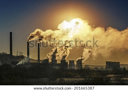 Factory pipe polluting air against sunset, environmental problems - stock photo