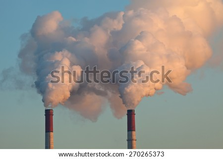 Factory pipes throwing out clouds of smoke and polluting the air - stock photo